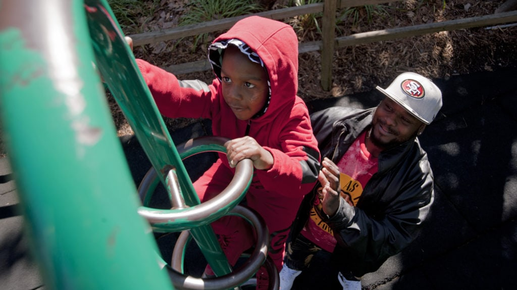 A father supports his young son while climbing playground equipment.