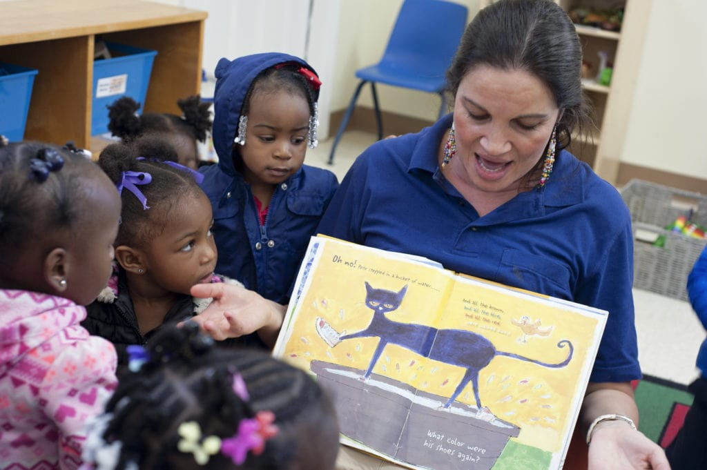 Preschool teacher reads a book to students in a classroom.
