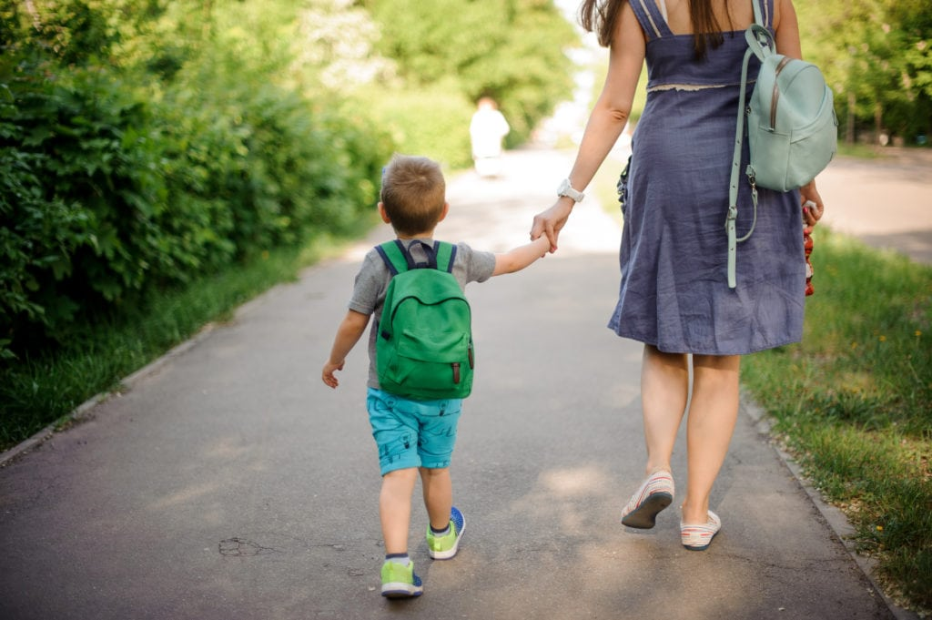 Back view of mother walking down the street with a young boy wearing a backpack on sunny summer day