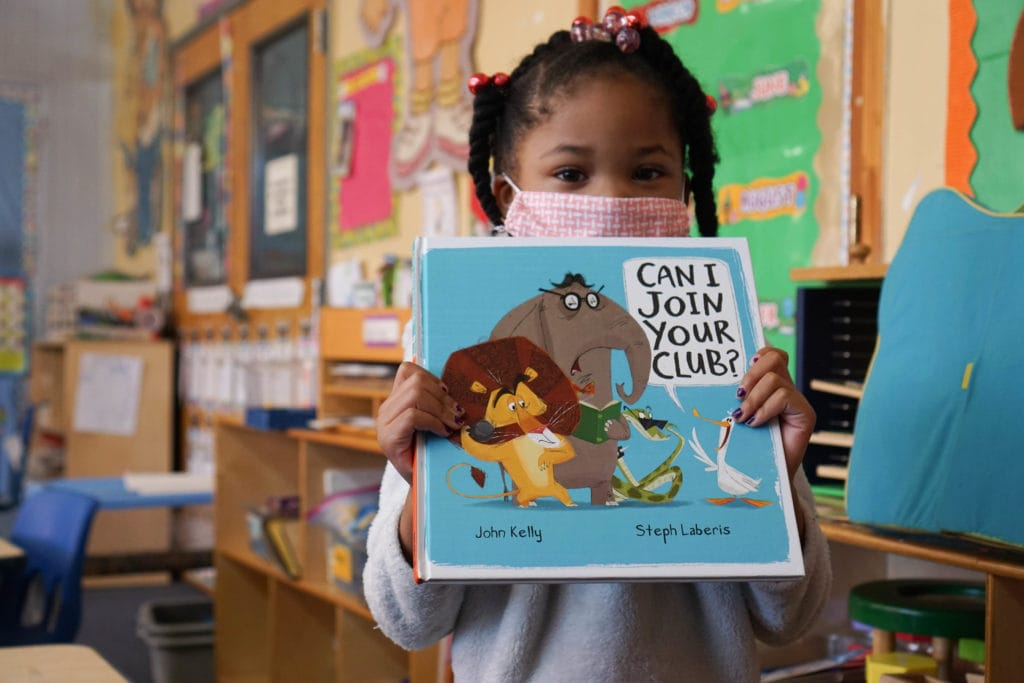 A child holds a book in a preschool classroom